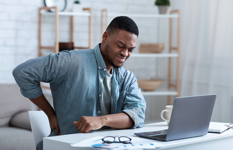 man sitting at desk with hand on lower back